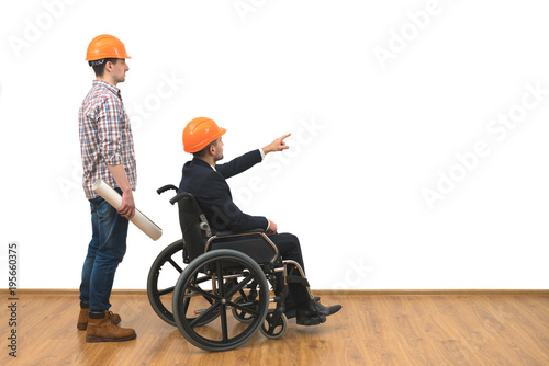 Photo  The two engineers with a wheelchair gesture on the white wall background