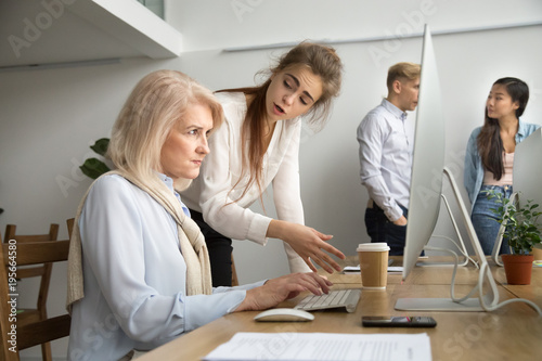 Fotografia  Young team leader correcting offended senior employee working on computer in off