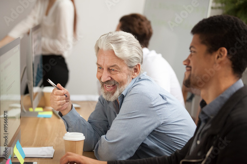 Photo Smiling senior employee discussing email with african colleague at workplace, ha