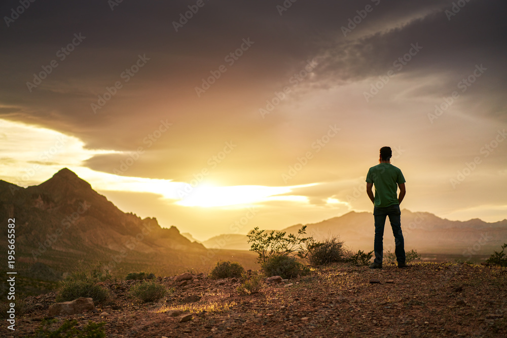Fototapeta man watching golden sunset over mountains in nevada desert