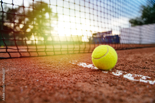 Close-up view of tennis ball near the net, on artificial red tennis court.