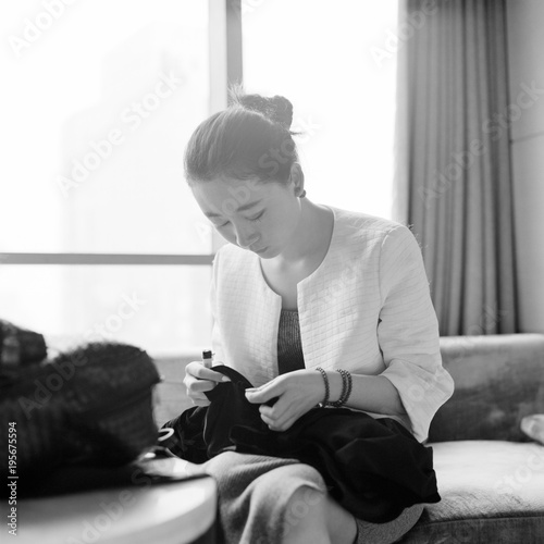 view of styled woman stitching coat at home