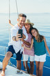 Family taking a selfie with smartphone in a sailboat.