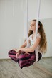 Curly cute girl practicing aerial yoga and sitting at lotus pose