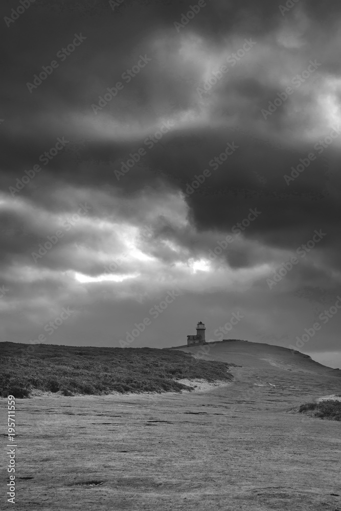 Stunning black and white landscape image of Belle Tout lighthouse on South Downs National Park during stormy sky