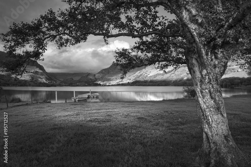 Poster Donkergrijs Black and white Landscape image of rowing boats on Llyn Nantlle in Snowdonia at sunset