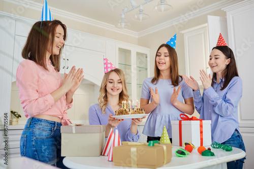 Plakat Grupa dziewczyn z ciastem ze świeczkami obchodzi urodziny w pokoju.