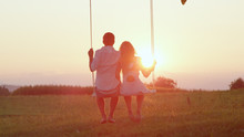 LENS FLARE SILHOUETTE Young Couple Swaying On Swing, Gazing Into Crimson Sunset