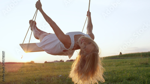 LENS FLARE CLOSE UP: Happy young woman smiles and leans back on swing in nature