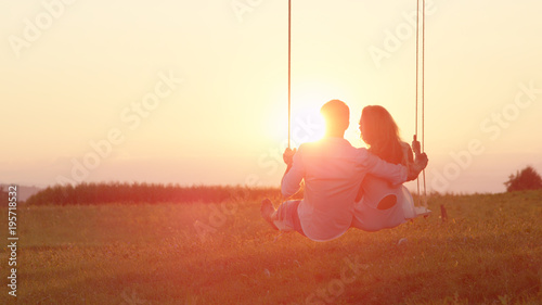 Photo  LENS FLARE: Happy couple swaying on a swing embraced on sunlit summer evening