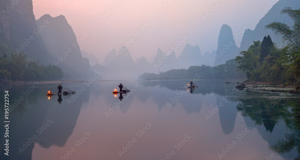Fototapeta The Li River, Xingping, China, scenic landscape. Cormorant fishermans on the ancient bamboo boats with a lighted lamps at sunrise.