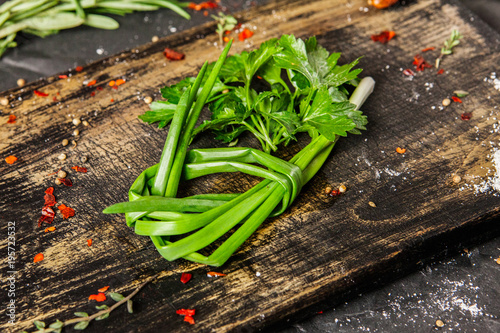 Green onion and parsley on wooden cutting board. Close up.
