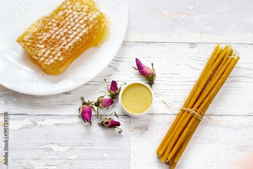 Fotografie, Obraz  organic tasty honeycomb, honey lip balm, pink wild roses and natural candles
