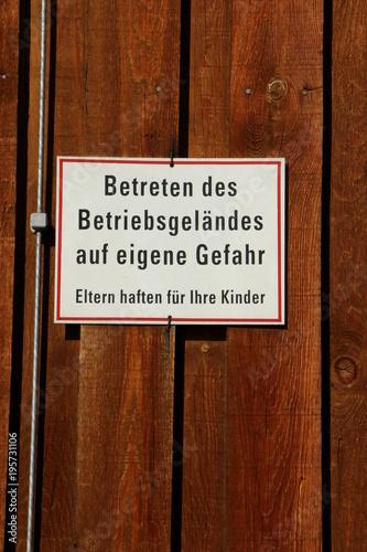 Photo German Sign: Enter the premises at your own risk, Schild vor einem Betriebsgel