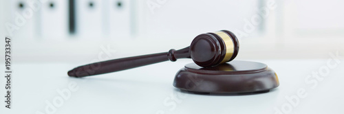 Fotografie, Obraz  Brown wooden judge gavel lies on a wooden plate on white table.