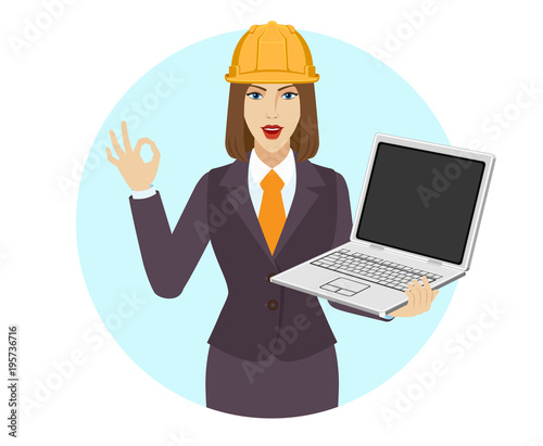 Photo Businesswoman in construction helmet  holding a laptop notebook and show a okay