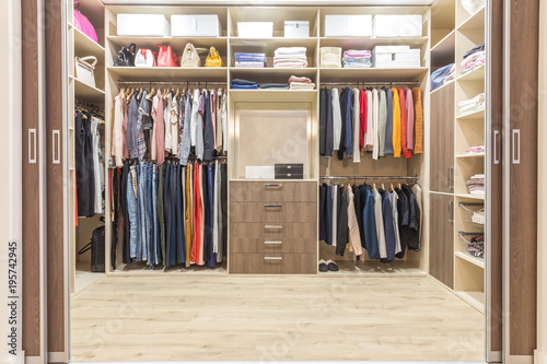 Fotografía  Modern wooden wardrobe with clothes hanging on rail in walk in closet design int