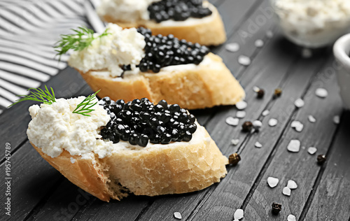 Sandwiches with delicious black caviar and cottage cheese on wooden board