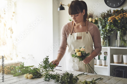 Florist putting together a mixed flower arrangement in her shop