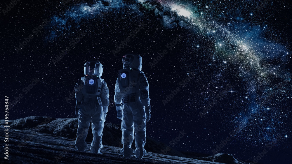 Fototapeta Crew of Two Astronauts in Space Suits Standing on the Moon Looking at the The Milky Way Galaxy. High Tech Concept of Moon Colonization and Space Travel.
