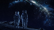 Crew Of Two Astronauts In Space Suits Standing On The Moon Looking At The The Milky Way Galaxy. High Tech Concept Of Moon Colonization And Space Travel.