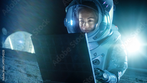 Female Astronaut Wearing Space Suit Works on a Laptop