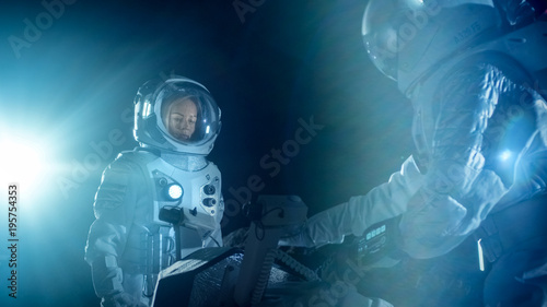 Two Astronauts in Space Suits on an Alien Planet Prepare