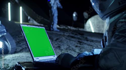 Vászonkép Astronaut on the Alien Planet Works on a Mock-up Green Screen Laptop