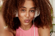 Close up shot of dark skinned funny African American woman makes grimace as poses for making selfie, listens audio book or favourite music in headphones, has spare time after work or studying