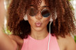 Pretty curly African American female student rests in university canteen during break, wears trendy sunglasses, poses for selfie with unrecognizable electronic device, listens music in headphones