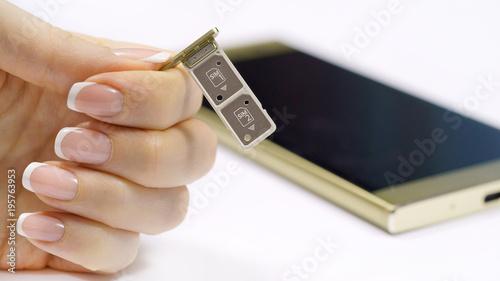 a female hand holds a dual SIM card slot  Nano SIM and