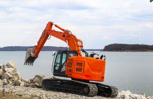 Shiny new orange backhoe on tracks by lake arranging big