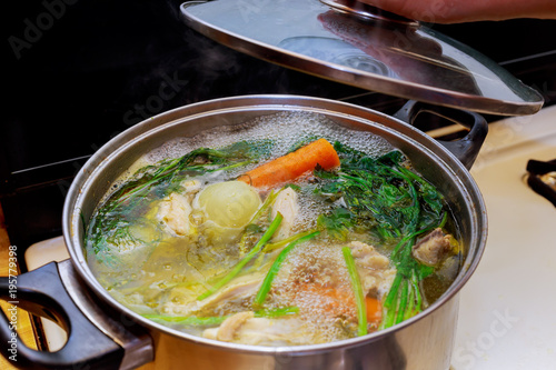 Ingredients for preparing chicken bone broth in a pot chicken, onions, celery root, carrots, parsley