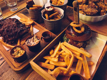 Classic BBQ Table With Spare Ribs,chicken Wings, Hamburgher With Frayed Pig, Onion Rings, Chips. Wooden Rustic Background. Top View.