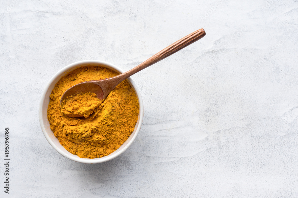Fototapety, obrazy: Golden turmeric powder and wooden spoon. Concrete background. Traditional indian spice. Top view.