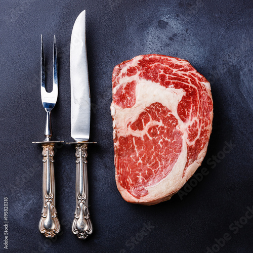 Photo  Raw fresh marbled meat Steak Rib eye Black Angus and fork and knife on dark back