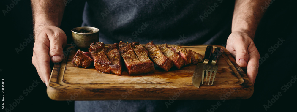 Fototapety, obrazy: Man holding juicy grilled beef steak with spices on cutting board