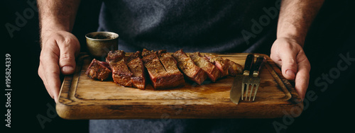 Poster de jardin Steakhouse Man holding juicy grilled beef steak with spices on cutting board