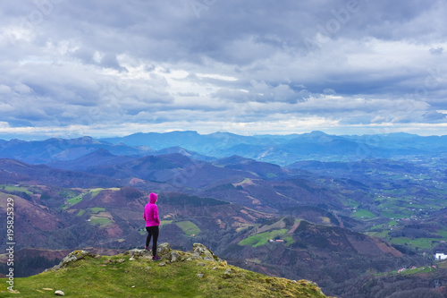 Fototapeta Hiker looking at the landscape in the Aiako Harriak natural park with the mountains of Gipuzkoa in the background obraz na płótnie