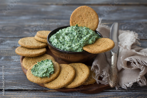 Green spinach dip with cream cheese, garlic and spices on a wooden board with oat crackers, rustic style, selective focus. Healthy homemade food