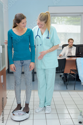 Fototapety, obrazy: woman using weight scale balance with doctor in clinic