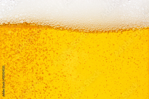 Fotografia  Pouring beer with bubble froth in glass for background on front view wave curve
