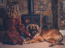 Woman With Dog Relaxing By Fire