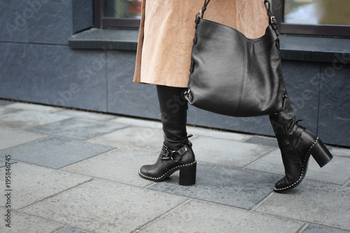Fototapeta Stylish woman in black shoes walking down the street obraz