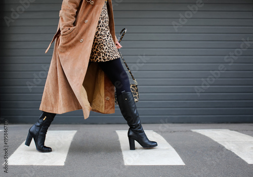 Fototapeta Stylish woman in black shoes walking across the street obraz