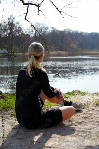 Fotobehang Ontspanning Blonde athlete girl sitting on ground to relax after jogging with water bottle under a tree on a lake shore lit by sunlight - Runner girl in sportswear having a break after training - copy space