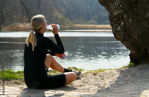 Young Blonde athlete fitness woman drinking water after jogging workout