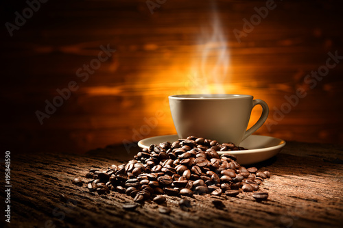 Deurstickers koffiebar Cup of coffee with smoke and coffee beans on old wooden background