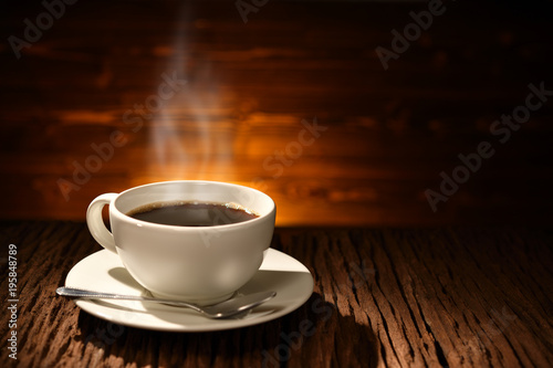 Wall Murals Cafe Cup of coffee with smoke on old wooden background