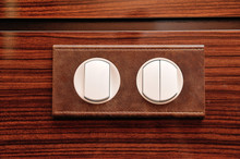 Luxury Light Switch, Leather Trimmed And Mounted On A Wooden Polished Wall